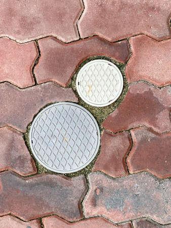 Small circle manhole cover on the brick floor Archivio Fotografico