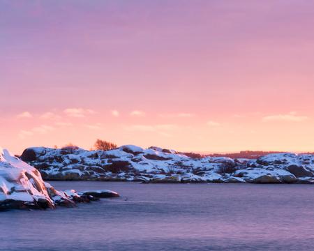 Pink sunset over rocky island at west coast of gothenburg,Sweden Stock Photo