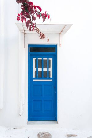 Narrow streets and blue windows with white buildings in Mykonos Greece