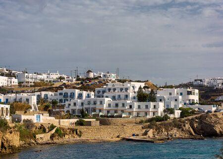 Landmark white buildings lined up on sea shore  in the town of mykonos greece Stok Fotoğraf