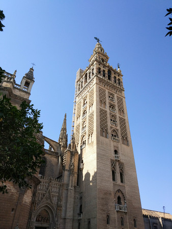 View of the Giralda of the Cathedral of Seville Photograph taken on clear day without clouds, against light and blue sky Редакционное