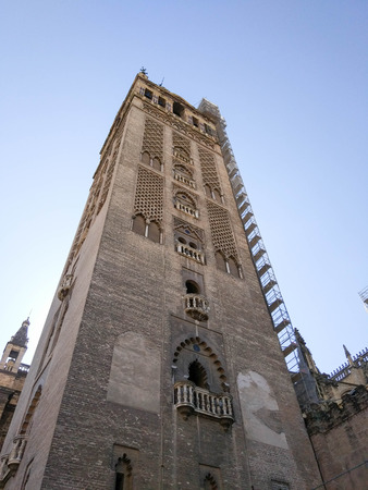 View from below next to the Giralda of Seville next to Seville Cathedral, Photograph taken on clear day without clouds, against light and blue sky - Photograph taken on October 31, 2017, Seville, Andalucia, Spain, Europe