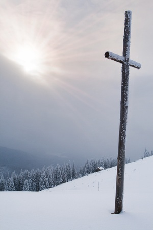 catholic cross in the mountains in winter photo