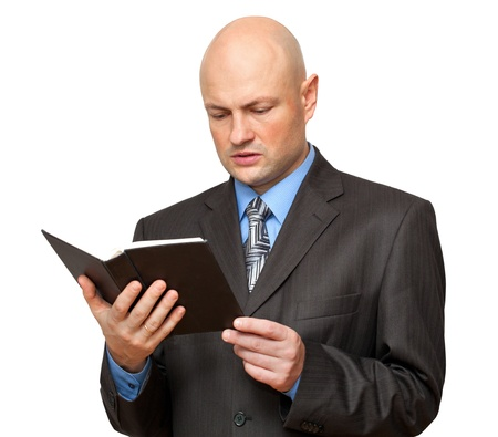 Bald man in suit reads a Bible  Isolated on white photo