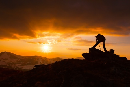 silhouette of a photographer who shoots a sunset in the mountains Stock Photo