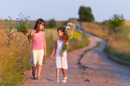 Two girls walking along the road with a bouquet of flowers Stock Photo - 13055956