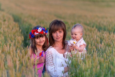 Mother and her two daughters in a field of wheat photo