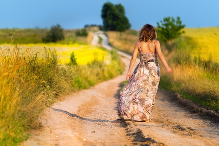 Beautiful white girl walking the road before sunset Stock Photo