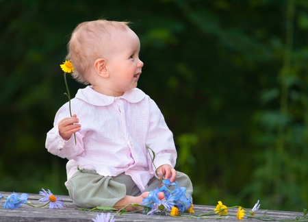 Adorable one-year baby sitting on the table with flowers and smiling Stock Photo - 13055949