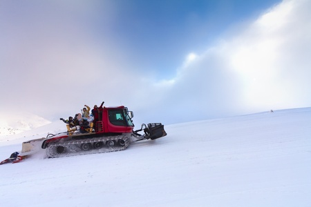 snow grooming machine: Snowcat with people going up the hill