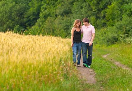Jong paar lopen op de weg in een veld van tarwe