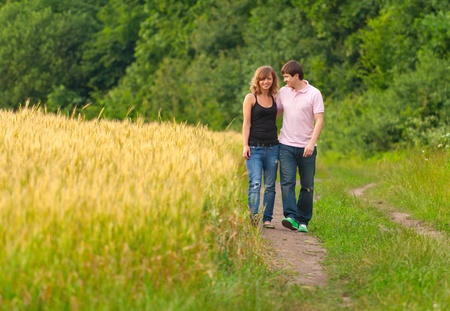 Young couple walking on the road in a field of wheat  photo