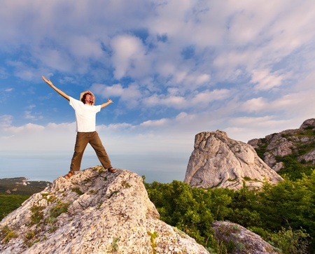 hiker at the top of a rock with his hands up enjoy sunny day photo