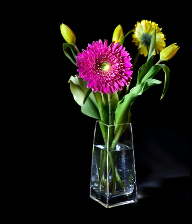 Bright flower bouquet in glass vase isolated over black background photo