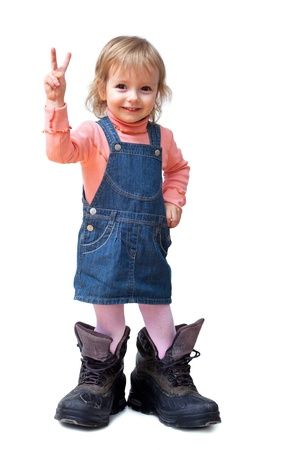 Smiling cute little girl in old big tracking shoes shows V-sign isolated on white photo