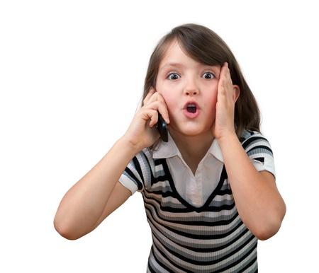 niÑos hablando: Linda niña de ocho años hablando en el teléfono celular aislado en blanco