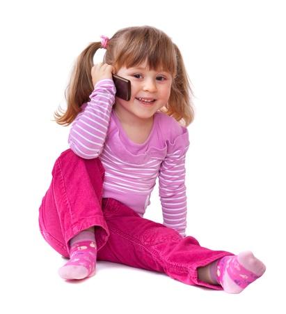 niños platicando: Niña linda está hablando por teléfono celular, aislado más de blanco