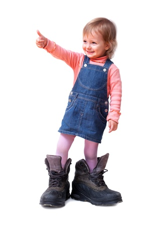 Smiling cute little girl in old big tracking shoes shows good-sign, isolated on white photo