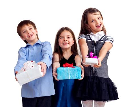 Drie schattige kinderen geven geschenken Geà ¯ soleerd op wit