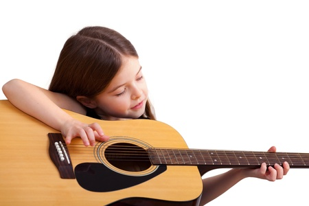 6 years old girl plays on the guitar, isolated on white photo