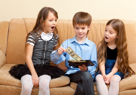 boy shows a wallet of dollars to two impressed girls photo