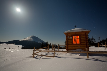 A small chapel in the mountains at the winter. Night with moon and stars photo