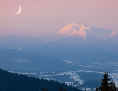 Moon over snow-covered peak. Early morning photo