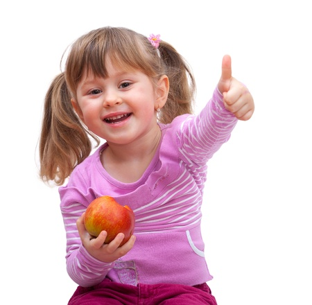adorable little girl eating an apple and show good sign, isolated against white background photo