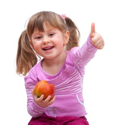 comida rica: niña adorable que come una manzana y mostrar buena señal, aislado contra el fondo blanco