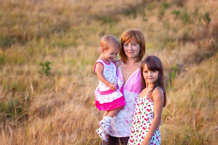 Mother and her lovely two daughter in wheat field photo
