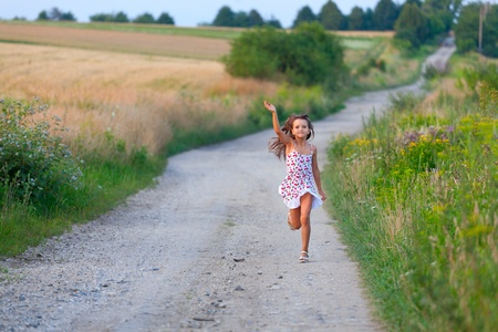 Cute seven years girl running in filds road on sunset summer day photo