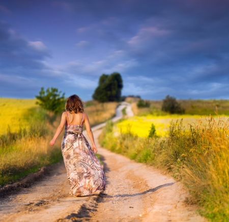 ways to go: Beautiful white girl walking the road before sunset Stock Photo