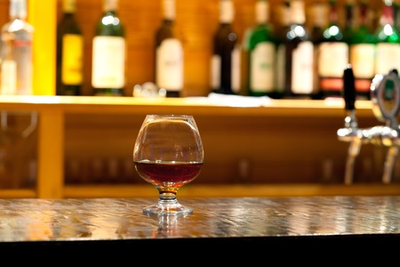 nightcap: Glass from whiskey and a bottle on a bar counter at restaurant