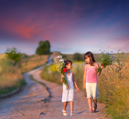 Two girls walking along the road with a bouquet of flowers