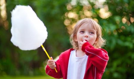 algodon de azucar: Llittle ni�a comiendo algod�n de az�car en el parque en primavera