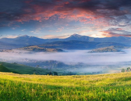 Summer landscape with a mountain village in the mist photo