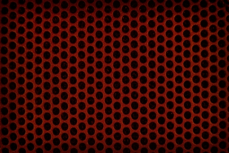 Dark red perforated plastic background photo