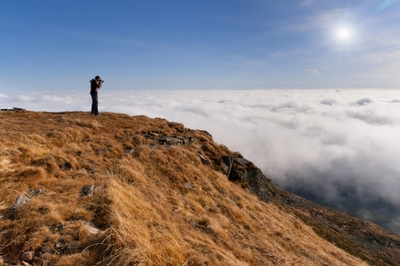 gleam: Photographer makes the photo above the clouds in the mountains Stock Photo