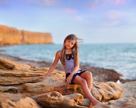 little girl sitting: Cute little girl on the beach