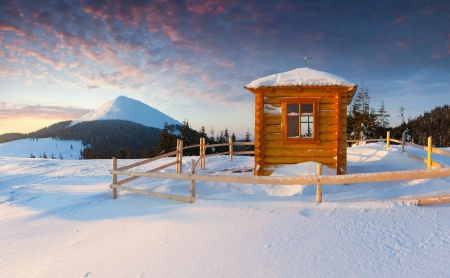 A small chapel in the mountains at the winter morning photo