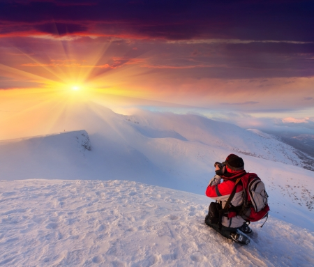 takes: Photographer takes a sunset in the mountains Stock Photo