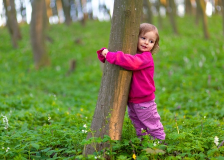 Cute little girl hugging a tree trunk in the spring forest Фото со стока