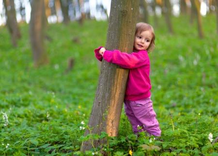 Niña linda que abraza un tronco de árbol en el bosque de la primavera