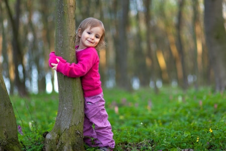 Cute little girl hugging a tree trunk in the spring forest photo