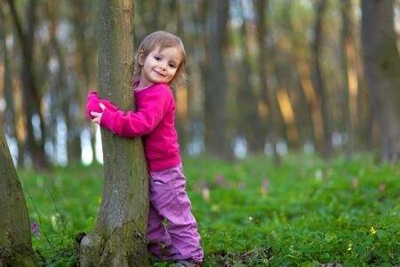 Cute little girl hugging a tree trunk in the spring forest Zdjęcie Seryjne