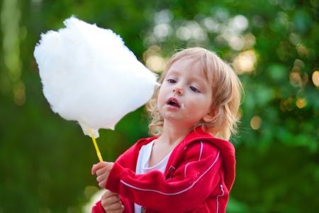 algodon de azucar: Llittle chica comiendo algod�n de az�car en el parque en primavera