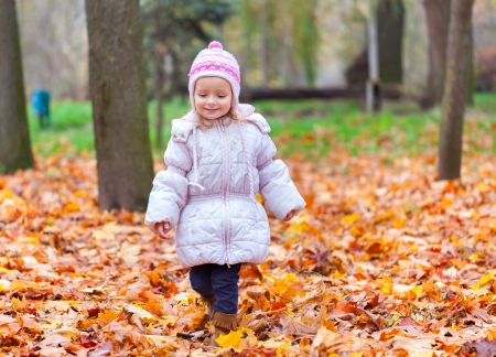 Little girl walking in the autumn park photo