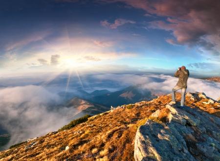 Fotograaf neemt een zonsondergang in de bergen