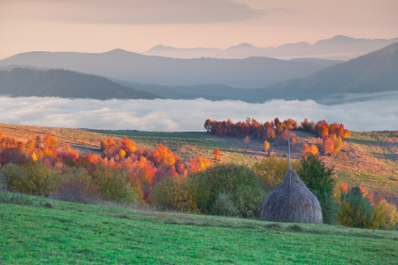 Foggy autumn morning in the mountain village photo