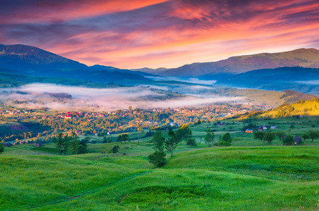 Summer morning in the mountain village. Colorful sunrise. photo